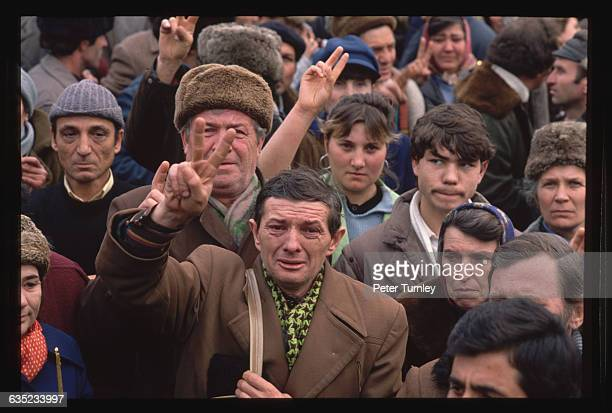 Avram Constantin of Bucharest weeps and flashes victory signs along with the gathered crowd on Christmas Day as he watches trucks go by bearing dead...