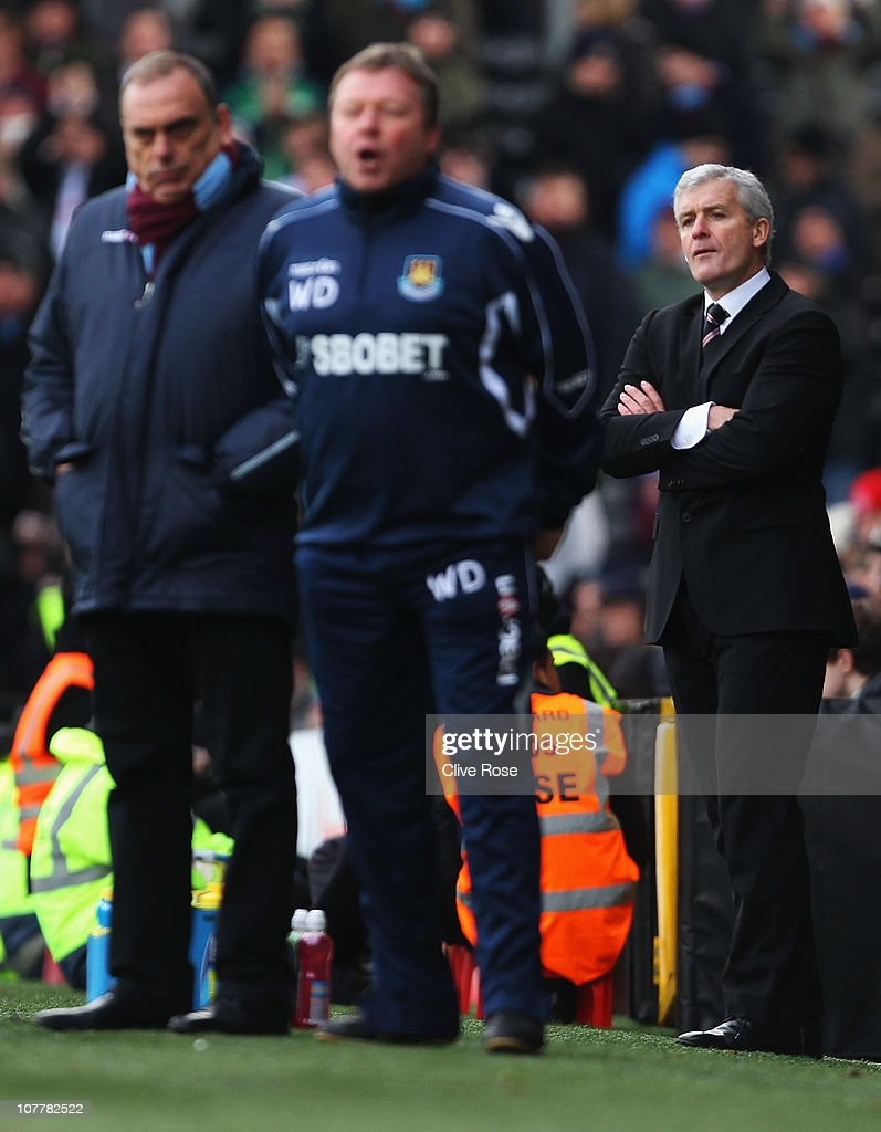 Avram Grant manager of West Ham United, coach Wally Downes and Mark Hughes manager of Fulham look on during the Barclays Premier League match between Fulham and West Ham United at Craven Cottage on December 26, 2010 in London, England.