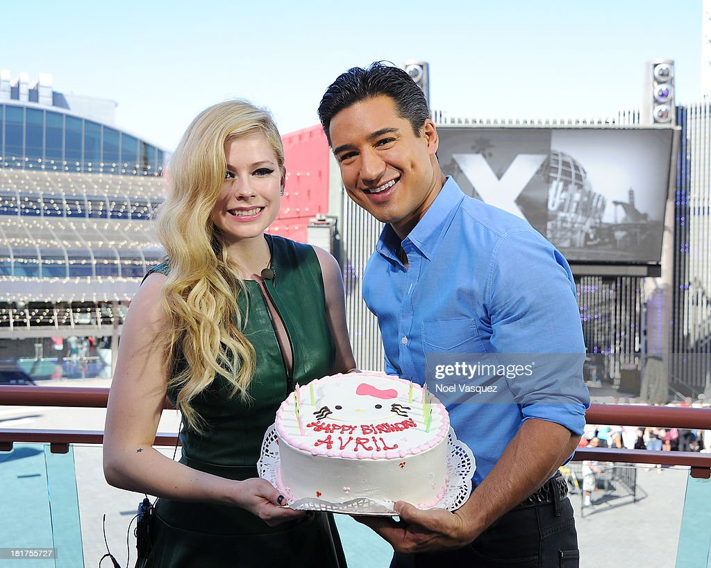 Avril Lavigne displays her birthday cake with Mario Lopez on 'Extra' at Universal Studios Hollywood on September 24, 2013 in Universal City, California.