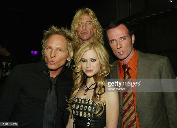 Avril Lavigne poses with Velvet Revolver band members Matt Sorum Duff McKagan and Scot Weiland backstage during the 2004 World Music Awards at the...