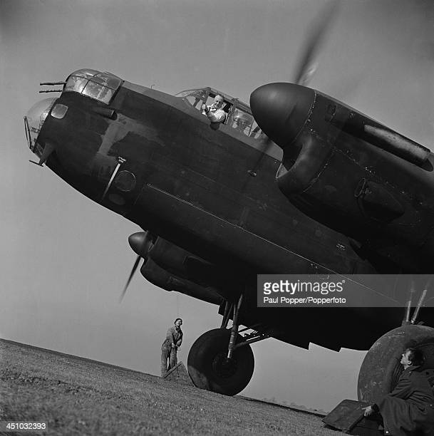 Avro chief test pilot Captain Harry Albert 'Sam' Brown signals to ground crew to remove the chocks before takeoff in an Avro Lancaster heavy bomber...