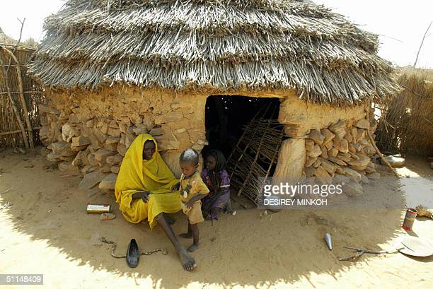 Awa and her two children who escaped from the Janjaweed Arab militias sit by their house in the village of Kour in Darfur 28 July 2004 The Sudanese...
