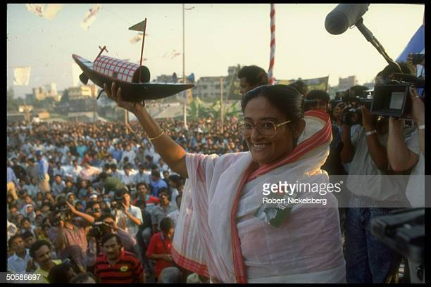 Awami League ldr Sheik Hasina Wazed on stump holding boat during crowded election campaign rally
