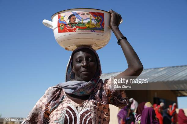 Awaradi Refugee Settlement, Diffa, Niger. December 11 2019. A Nigerian woman holds a bowl of rice aloft in the Awaradi refugee camp in Niger.