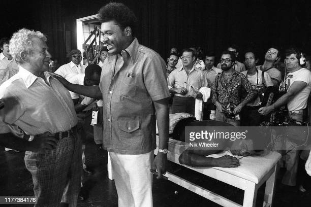 Award winning novelist Norman Mailer jokes with boxing promoter Don King while heavyweight boxer Muhammad Ali lies on the massage table in his...