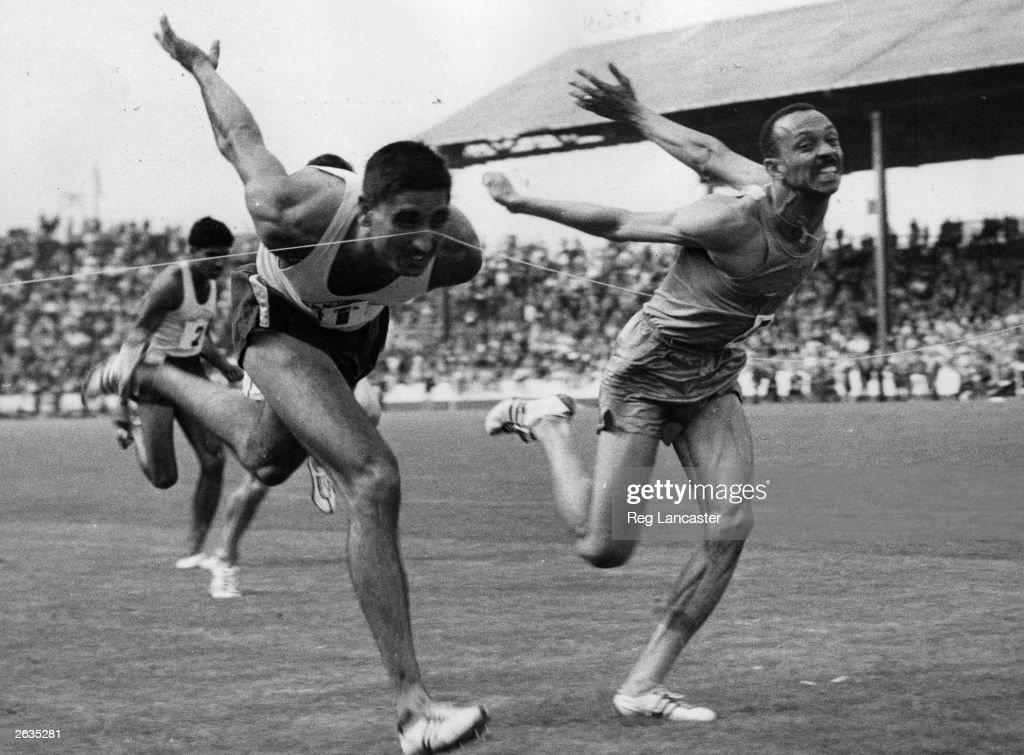 Award winning sports photograph showing an unidentified runner crossing the finish line, the line itself on his nose.