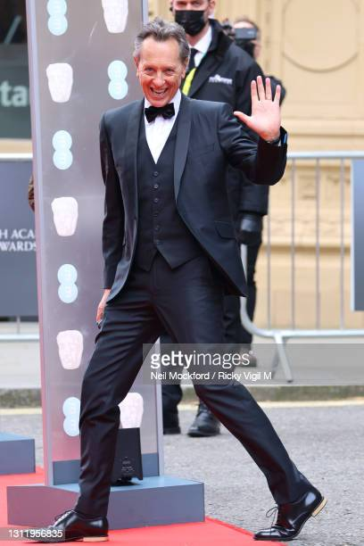 Awards Presenter Richard E. Grant seen arriving at the EE British Academy Film Awards 2021 at the Royal Albert Hall on April 11, 2021 in London,...