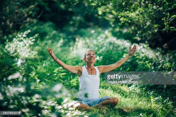 awareness meditation. mindful woman sitting on the ground with open arms - belgrade serbia stock pictures, royalty-free photos & images