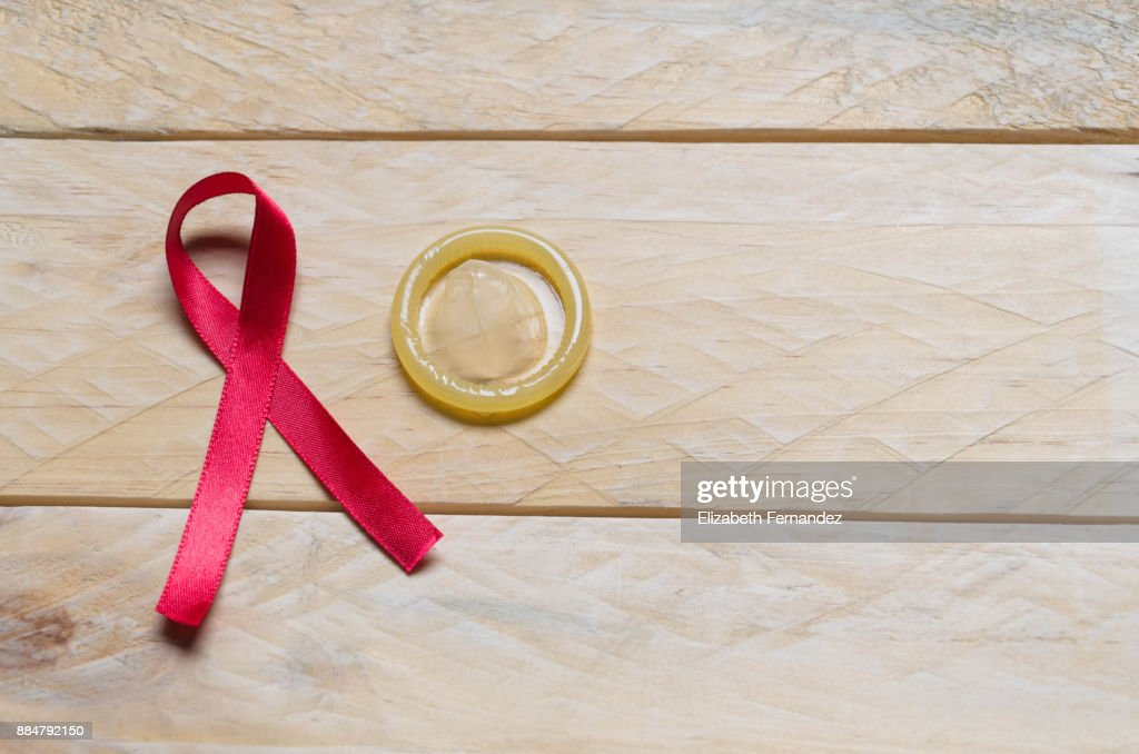 AIDS awareness red ribbon and condom : Stock Photo