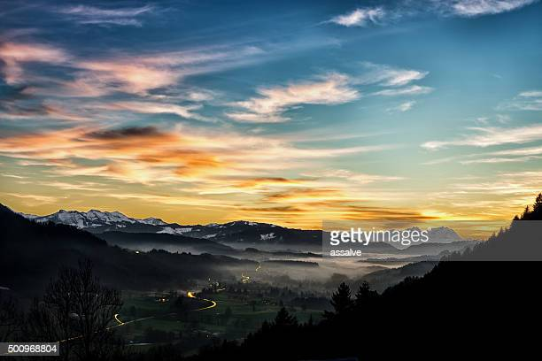 Awe alpine sundown with fog and car light trails