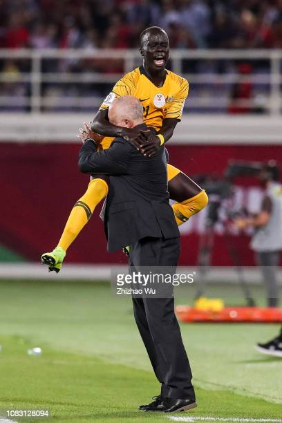 Awer Mabil of Australia celebrates his scoring with Graham Arnold coach of Australia during the AFC Asian Cup Group B match between Australia and...