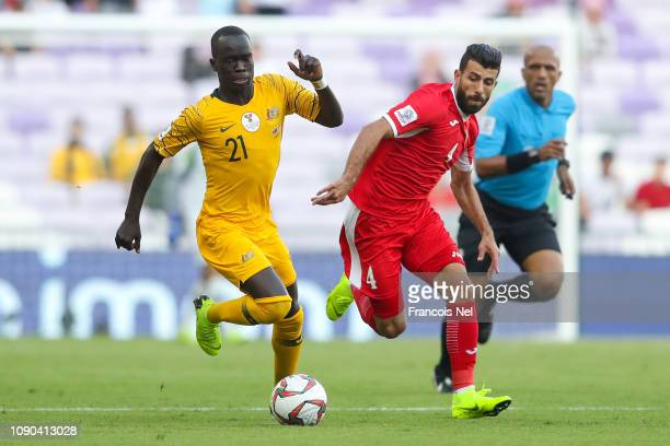 Awer Mabil of Australia competes for the ball with Baha' AbdelRahman of Jordan during the AFC Asian Cup Group B match between Australia and Jordan at...