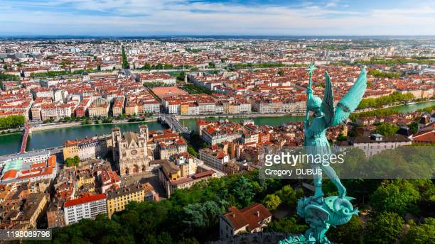 awesome aerial view on lyon french cityscape viewed from the roofs of basilica notre dame de fourviere with archangel michael statue overlooking the city - auvergne rhône alpes stock pictures, royalty-free photos & images