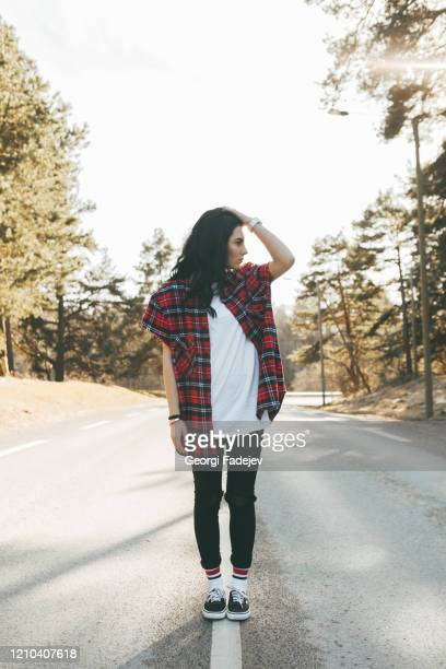 awesome girl in trendy clothes standing on the road at the forest. beautiful look, spring. soft colours. - look back at early colour photography imagens e fotografias de stock