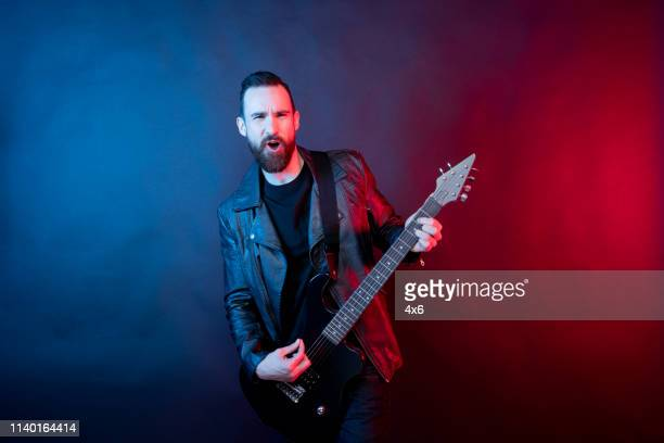 awesome guitarist rocking out with electric guitar - male likeness stock pictures, royalty-free photos & images