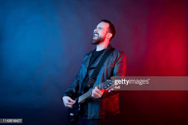 awesome guitarist rocking out with electric guitar - gel effect lighting stock photos and pictures