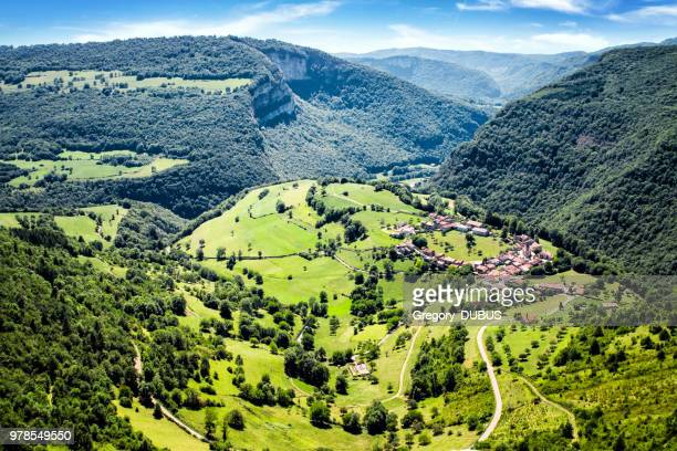 awesome landscape view of small old french village in circle shape in valley of bugey mountains in ain - rhone alpes stock photos and pictures