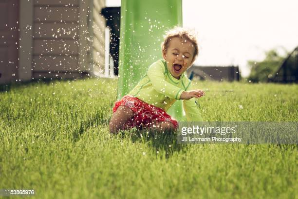 awesome photograph of 3 year old toddler uses slide in the summer with water outside at home - 滑る ストックフォトと画像