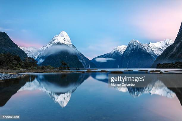 awesome sunrise at milford sound, new zealand - symmetry stock pictures, royalty-free photos & images