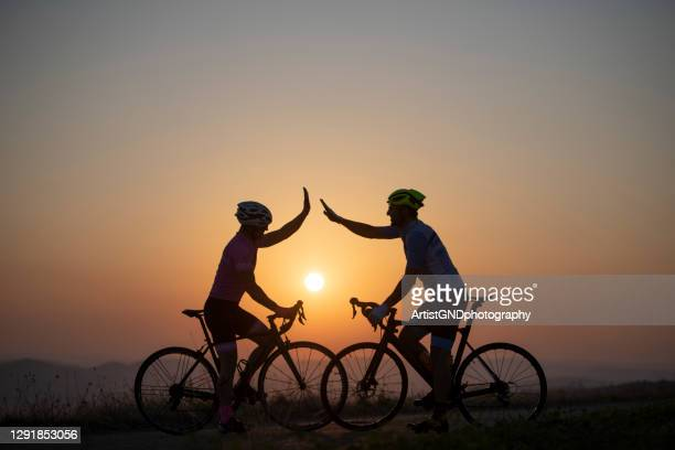 awesome track today, two road cyclist give five at sunset. - sports race stock pictures, royalty-free photos & images