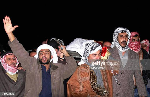 Iraqis chant slogans as they carry the bodies of Saddam Hussein's henchmen Barzan Ibrahim alTikriti and Awad Ahmed alBandar late 15 January 2007...