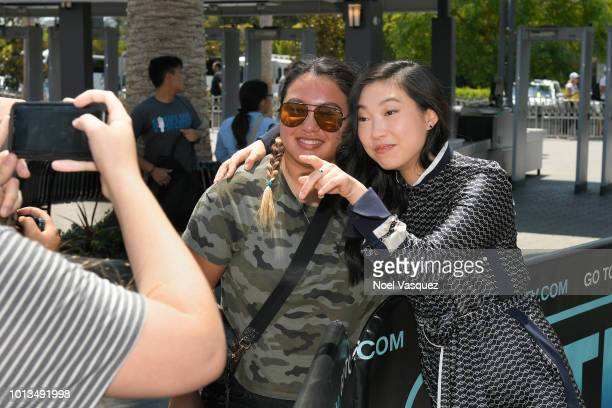 Awkwafina poses with a fan at Extra at Universal Studios Hollywood on August 8 2018 in Universal City California