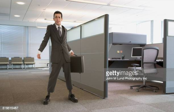 Awkward Hispanic businessman standing with briefcase in office