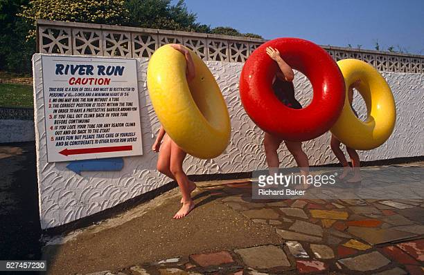 Awkwardly carrying their giant rubber rings by wrapping their left hands over the top curves three kids make their way tentatively down a ramp of...
