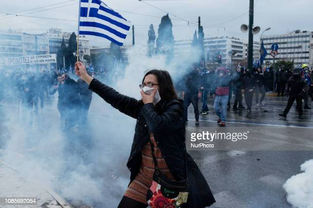 Awoman holds the Greek flag during riots in a rally over Macedonia name row in Syntagma square central Athens on January 20 2019 Violent clashes...
