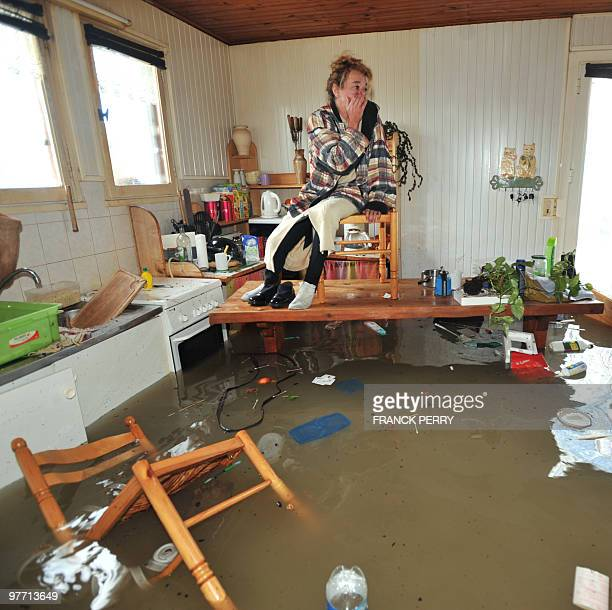 Awoman waits for rescuers in her kitchen on February 28 as a result of heavy floods in La FautesurMer western FranceDubbed 'Xynthia' the Atlantic...