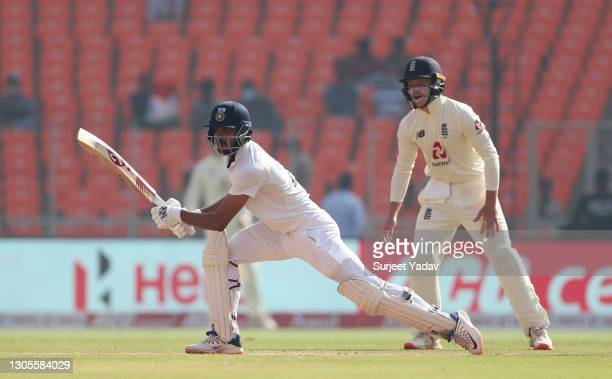 Axar Patel of India hits runs watched on by Ollie Pope of England during Day Three of the 4th Test Match between India and England at the Narendra...