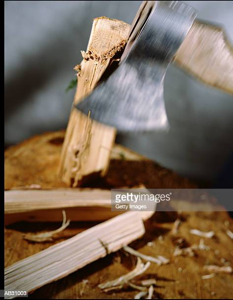 Axe splitting block of wood into two pieces, close-up