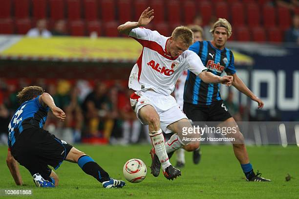 Axel Bellinghausen of Augsburg battles for the ball with Markus Kroesche of Paderborn and his team mate Soeren Brandy during the Second Bundesliga...
