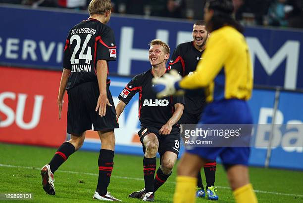 Axel Bellinghausen of Augsburg celebrates his team's first goal with team mates Daniel Brinkmann and Sascha Moelders during the Bundesliga match...