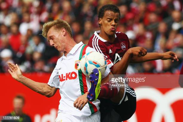 Axel Bellinghausen of Augsburg is challenged by Timothy Chandler of Nuernberg during the Bundesliga match between 1. FC Nuernberg and FC Augsburg at...