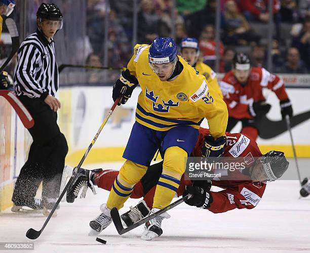TORONTO ON DECEMBER 31 Axel Holmstrom muscles Jason Fuchs off the puck as Sweden plays Switzerland in the round robin of the IIHF World Junior Hockey...