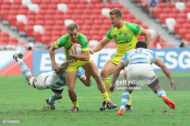 Axel Muller of Argentina tries to tackle John Porch of Australia during the 2016 Singapore Sevens at National Stadium on April 16 2016 in Singapore