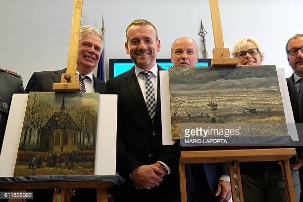 TOPSHOT Axel Ruger Director of the Van Gogh museum poses next to two recently recovered stolen paintings by late Dutch artist Vincent Van Gogh...