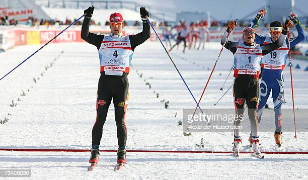 Axel Teichmann of Germany celebrates winning the first place whilst Tobias Angerer of Germany celebrates his 2nd place and Pietro Piller Cottrer of...
