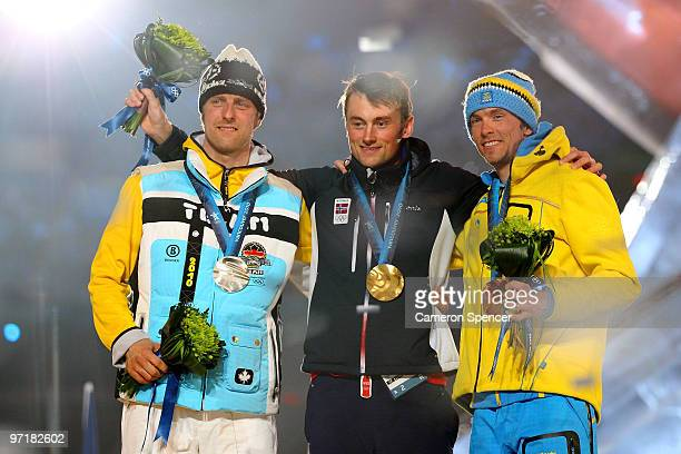 Axel Teichmann of Germany receives the silver medal Petter Northug of Norway receives the gold medal and Johan Olsson of Sweden receives the bronze...