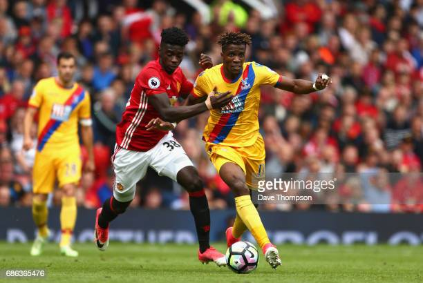 Axel Tuanzebe of Manchester United and Wilfried Zaha of Crystal Palace battle for possession during the Premier League match between Manchester...