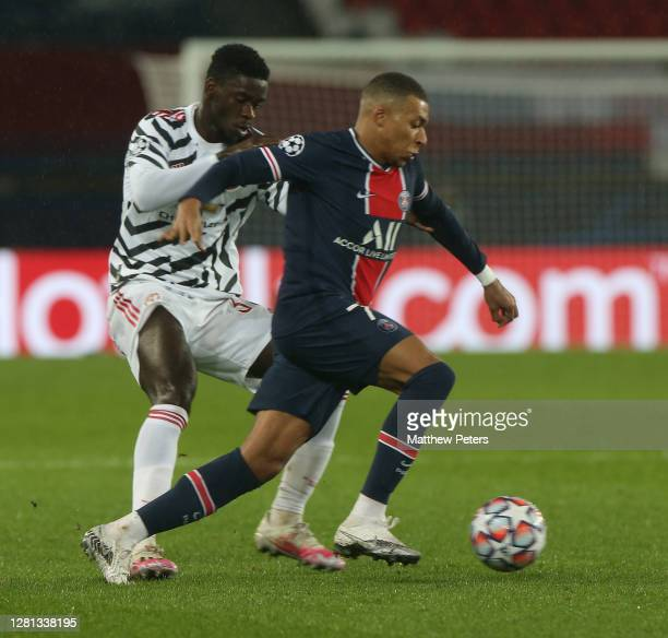 Axel Tuanzebe of Manchester United in action with Kylian Mbappe of Paris SaintGermain during the UEFA Champions League Group H stage match between...
