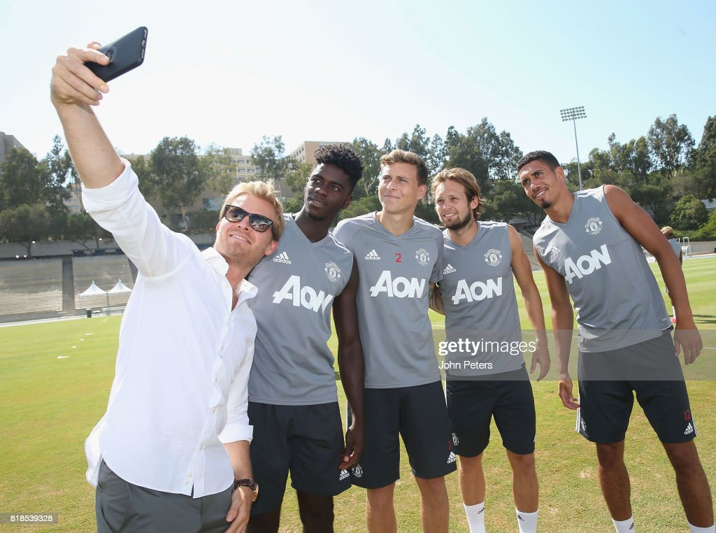Axel Tuanzebe, Victor Lindelof and Daley Blind and Chris Smalling of Manchester United take a selfie with Formula One world champion Nico Rosberg ahead of a first team training session as part of their pre-season tour of the USA at UCLA on July 18, 2017 in Los Angeles, California.