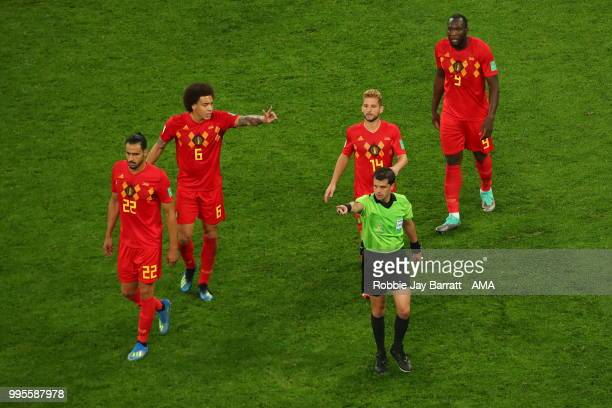 Axel Witsel of Belgium and Romelu Lukaku of Belgium and Dries Mertens of Belgium surround Match referee Andres Cunha after he fails to give a foul...
