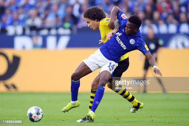 Axel Witsel of Dortmund is challenged by Rabbi Matondo of Schalke during the Bundesliga match between FC Schalke 04 and Borussia Dortmund at...