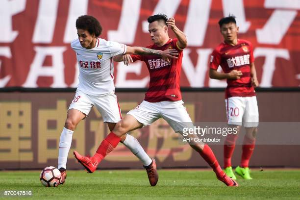 Axel Witsel of Tianjin Quanjian competes for the ball with Gao Lin of Guangzhou Evergrande during their Chinese Super League football match in...