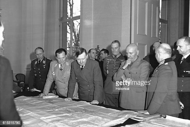 Axis dictators Hitler and Mussolini study maps surrounded by their aids