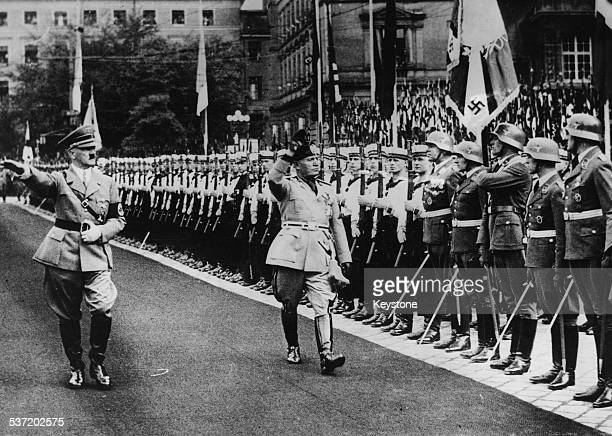 Axis leader Adolf Hitler and Benito Mussolini saluting as they inspect a Guard of Honor, Munich, 1937.