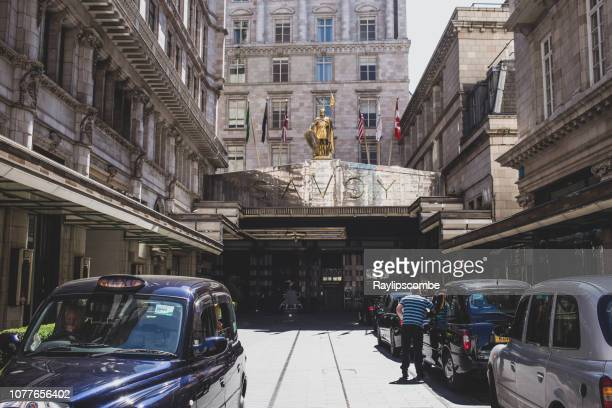 axi's parked outside the facade of the savoy hotel located along the strand in the city of westminster in central london. - the strand london stock pictures, royalty-free photos & images