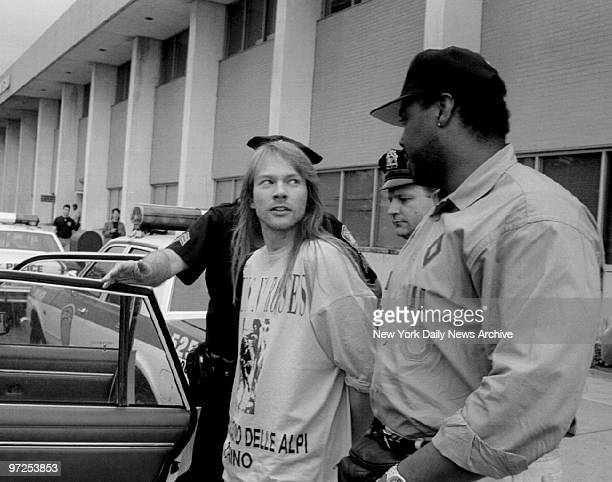 Axl Rose of the band Guns N' Roses looks toward his bodyguard as he is led to police car by two officers at Kennedy Airport